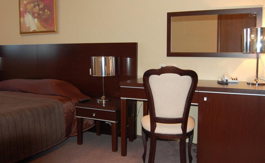 Двуспальная кровать, стул, большое зеркало в номере SUITE отеля HELIOPARK Residence