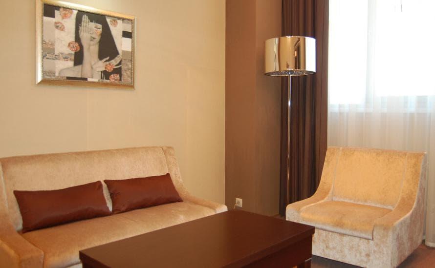 Диван и журнальный столик в номере отеля HELIOPARK Residence