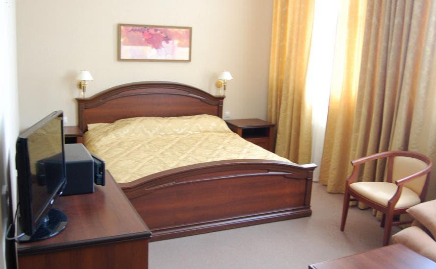 Двуспальная кровать в номере отеля HELIOPARK Residence